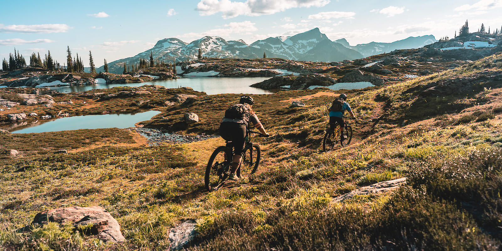 2 mountain bikers riding in alpine terrain at sol mountain lodge